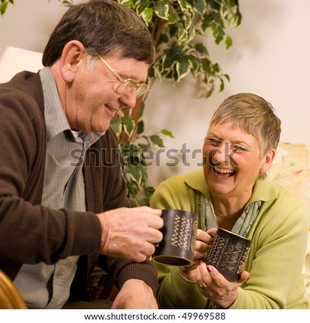 Senior man and woman couple relaxing on sofa in lounge, with drinks of tea or coffee - stock photo