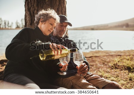 Senior man and woman enjoying outdoors camping on picnic area near Lake. Woman pouring wine in glasses, both sitting under a tree at campsite. - stock photo