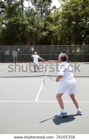 Senior man and woman playing in a tennis match. - stock photo