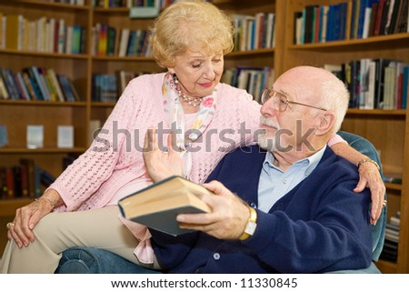 Senior man and woman reading together and discussing. - stock photo
