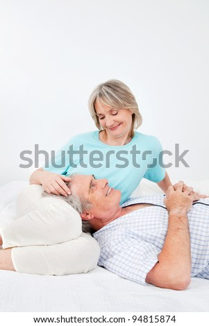Senior man and woman relaxing together in bedroom - stock photo