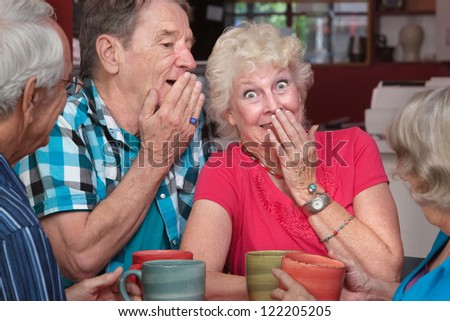 Senior man and woman sharing whispering as friends look on - stock photo