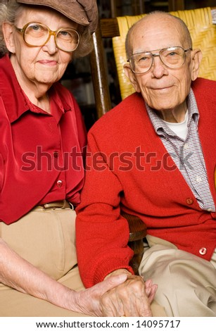 Senior Man and Woman Sitting Together Holding Hands.  Pleasant Look on Face. - stock photo