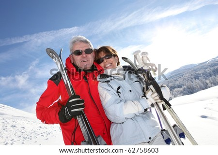 Senior man and woman smiling with skis in snow