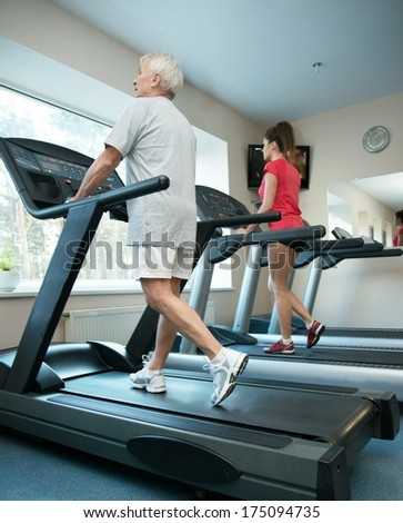 Senior man and young woman walking on a treadmill - stock photo
