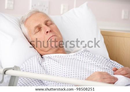 Senior man asleep in hospital bed - stock photo