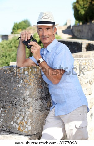 Senior man at a citadel with a pair of binoculars
