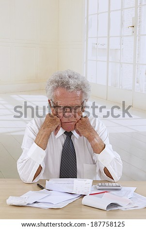 Senior man  at desk in shirt and tie holding his head and worrying about money.  - stock photo
