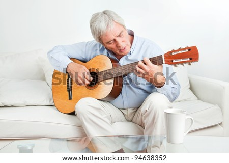 Senior man at home learning to play guitar