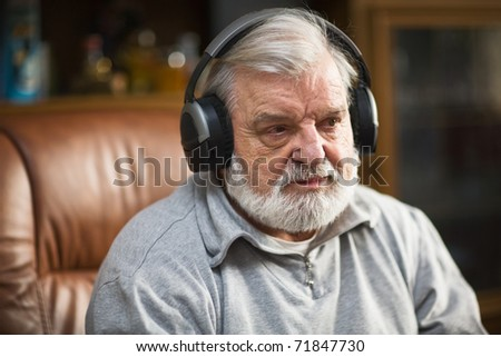 Senior man at home listening to music with headphones - stock photo