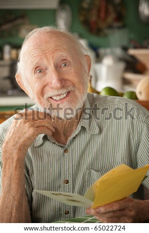 Senior man at home reading greeting card - stock photo