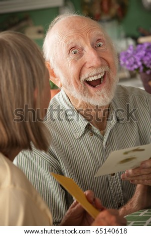 Senior man at home reading greeting card with wife - stock photo