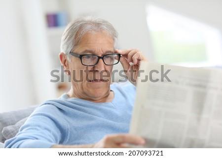 Senior man at home reading newspaper - stock photo