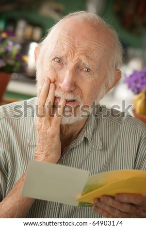 Senior man at home reading sympathy card - stock photo