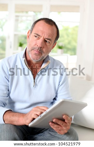 Senior man at home using electronic tablet - stock photo