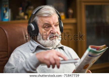 Senior man at home wearing headphones, holding magazine and remote control - stock photo