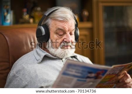 Senior man at home wearing headphones, reading magazine - stock photo