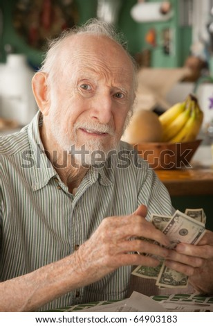 Senior man at home with a few dollars counting his money - stock photo