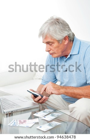 Senior man at home with calculator, laptop and Euro money
