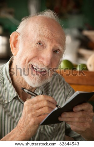 Senior man at home with checkbook - stock photo