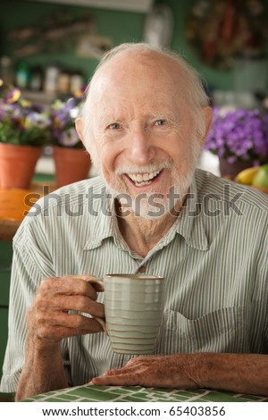 Senior man at home with coffee or tea - stock photo