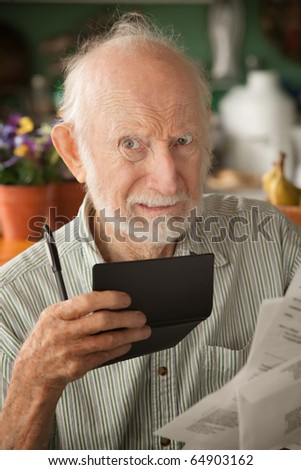 Senior man at home with many bills - stock photo