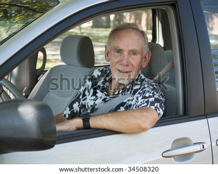 Senior man at wheel of car. Focus on face. - stock photo