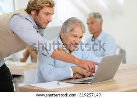 Senior man attending business class with trainer