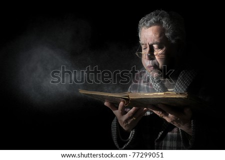 Senior man blowing dust of  a very old book isolated in black - stock photo