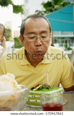 Senior man blowing out candle on cake