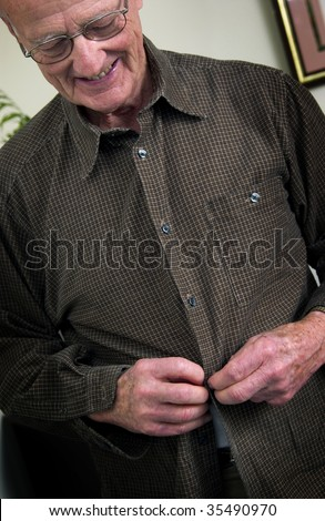 senior man buttoning shirt - stock photo