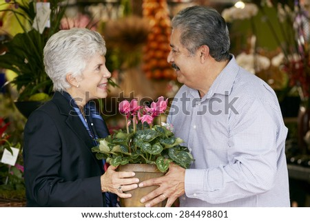 Senior Man Buying Plant As Gift For Wife - stock photo
