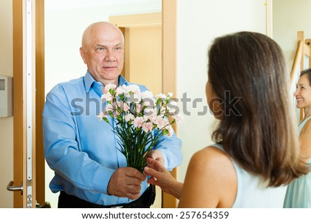Senior man came to mature woman with flowers at home door - stock photo