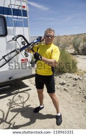 Senior man carrying bike - stock photo