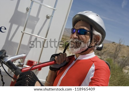 Senior man carrying bike