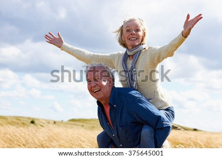 Senior Man Carrying Senior Woman On Walk In Countryside - stock photo