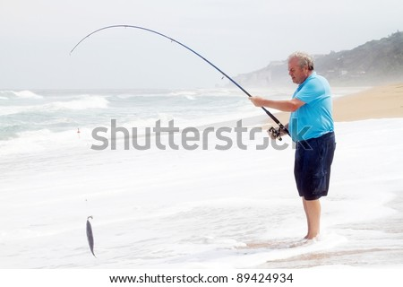senior man catching a fish with fishing rod on beach