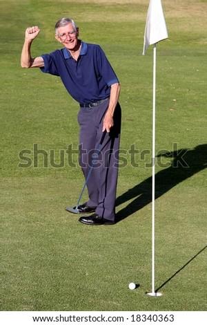 Senior man celebrating ball going into golf hole - stock photo