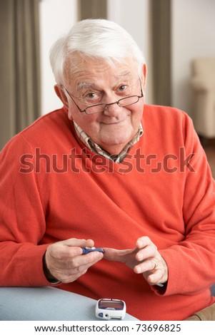 Senior Man Checking Blood Sugar Level At Home - stock photo