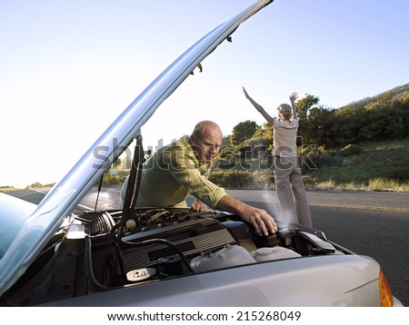 Senior man checking car engine at roadside, woman hailing oncoming traffic on country road - stock photo