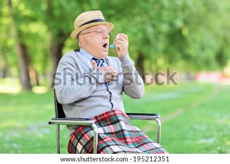 Senior man choking in park and holding an inhaler - stock photo