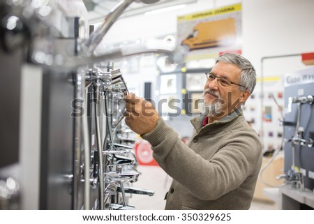Senior man choosing a bathroom/kitchen tap in a home furnishings retail store - stock photo