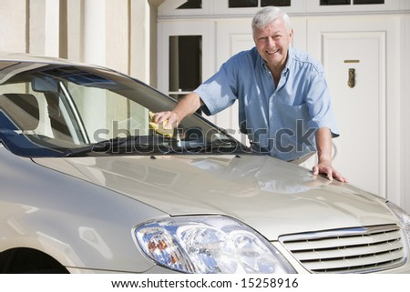 Senior man cleaning car outside house