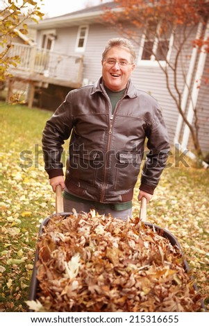 Senior man cleaning up fall leaves - stock photo