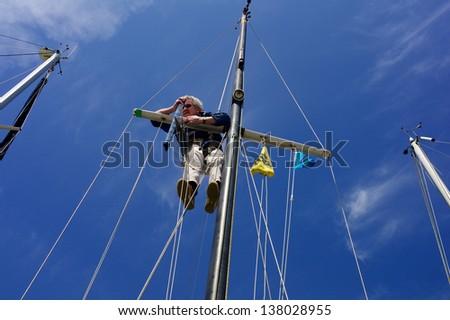 Senior man climbing the mast of a sailing boat - stock photo