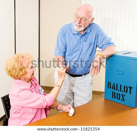 Senior man collects his I Voted sticker from a friendly volunteer. - stock photo