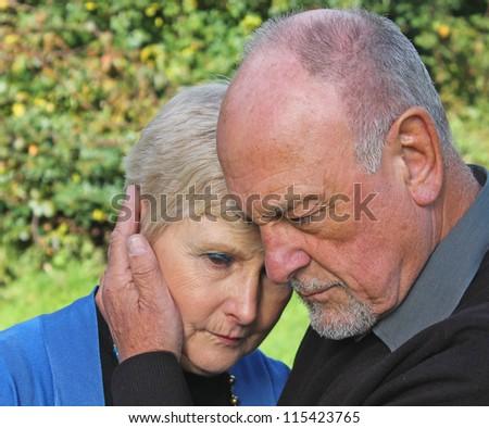 Senior man comforting beautiful wife - stock photo