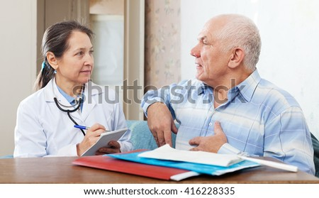 Senior man complaining to doctor about heartache - stock photo