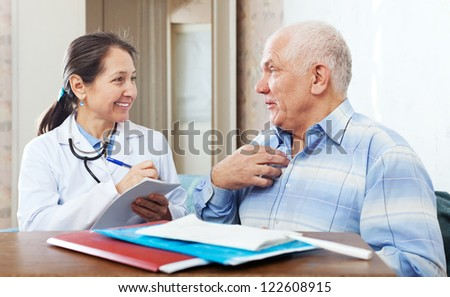 senior man  complaining to friendly doctor about malaise in interior - stock photo