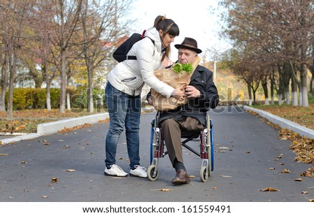 Senior man confined to a wheelchair by a leg amputation being helped with groceries by a woman carer in the street as they return from doing his shopping - stock photo